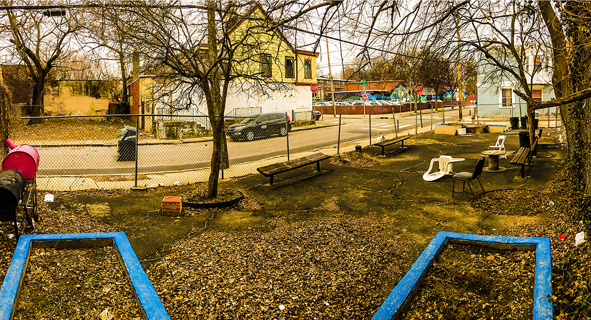 a wide angle photograph of Bringhurst Park, which is a small paved lot surrounded by a chain-link fence. There are empty raised garden beds at both ends of the park and a few trees and benches in the middle, as well as chairs and makeshift tables and a lot of fallen leaves.