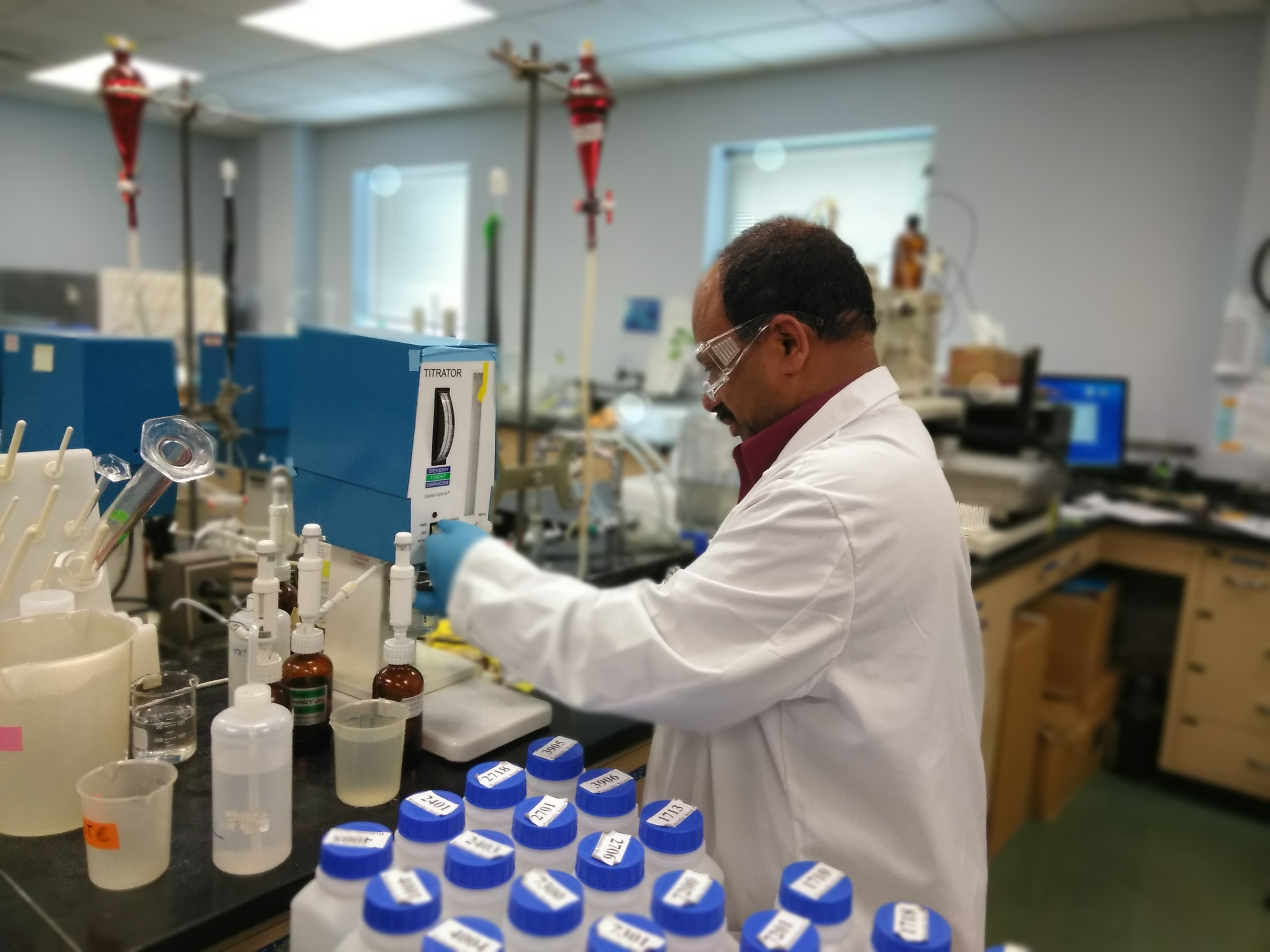 A photo of a scientist in a white lab coat, rubber gloves, and safety glasses uses a machine to test a water sample.