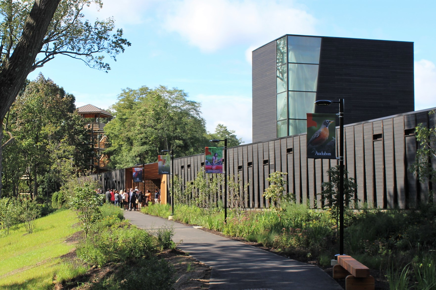 A photograph of the entrance to the new Discovery Center, shows off its modern architecture. Looking down the path lined with greenery and lampposts bearing flags featuring Audobon and Outward Bound activities and nature scenes, a crowd is gathered at the cedar-lined pass-through to the reservoir. In the background, a structure from the Outward Bound High Ropes Course can be seen through a gap in the trees.