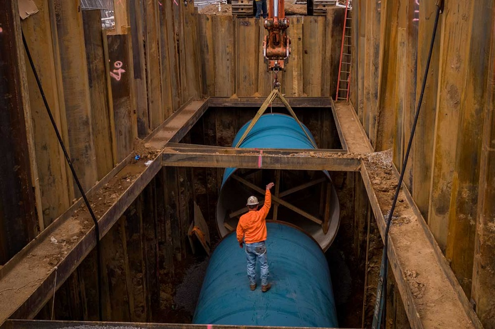 Water mains 10-feet in diameter are being installed underground. A man in a hardhat stands in a pit on one of the mains and helps direct a crane lowering another 10-foot pipe to connect to the other segment.