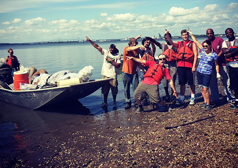A crew of volunteers celebrates after hauling an impressive load of trash from the Delaware River. Credit: Living Lands and Waters.