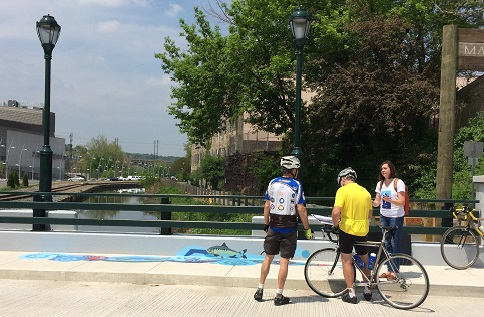 Cyclists in Manayunk stop to ask about the new Waterways artwork. Credit: Philadelphia Water.