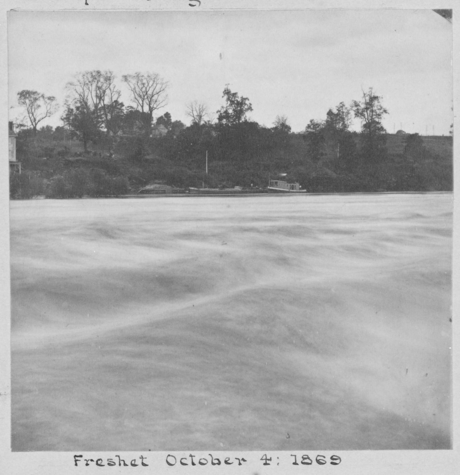 A historic photo shows waves of water rushing down the Schuylkill with boats tossed on the bank. The Fairmount Dam is invisible under the torrent.
