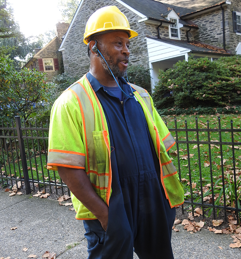 Lance Johnson, heavy equipment operator, is wearing a hard hat and safety vest and smiles as he talks. The big homes of East Falls are made of stone.