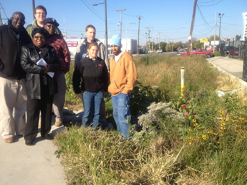 photo of a group from Southwest Community Development Corporation standing by one of the rain gardens they help maintain