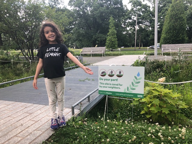 Yahara Spahr, 5, stands in a rain garden that the Centenial Parkside CDC helps care for. Her shirt says 'Little Feminist'.
