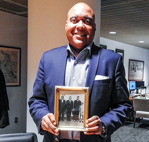 Commissioner Randy E. Hayman holds a photo in his office. It shows four men and a boy, all well dressed in suits except the boy, who has a white shirt with a big collar and shorts. The oldest man is to the left, and it does younger as you go to the right.