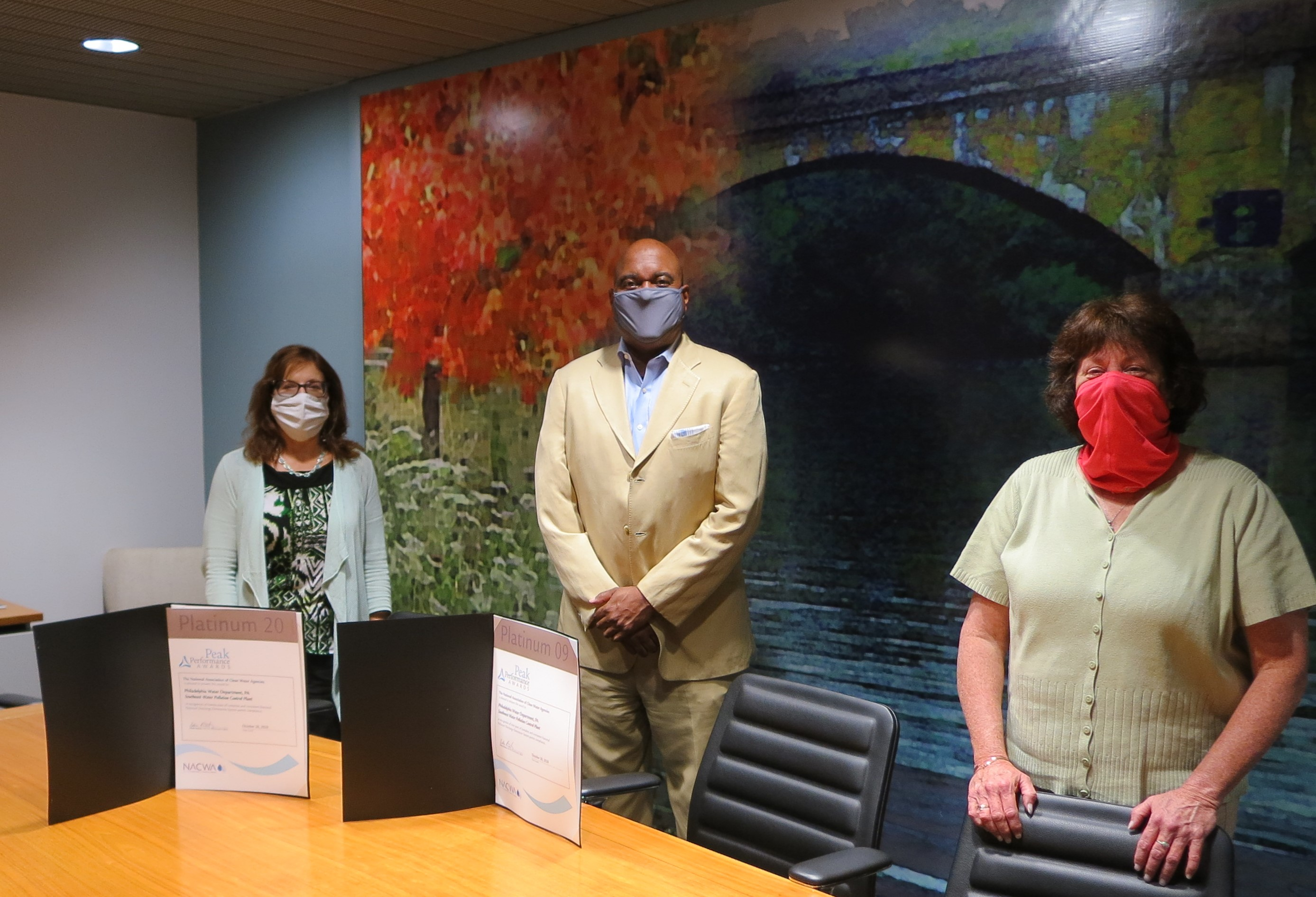 Mary Ellen Senss, Commissioner Hayman, and Donna Schwartz stand spaced out behind a conference table, wearing masks. The award certificates are propped up on the table in front of them.