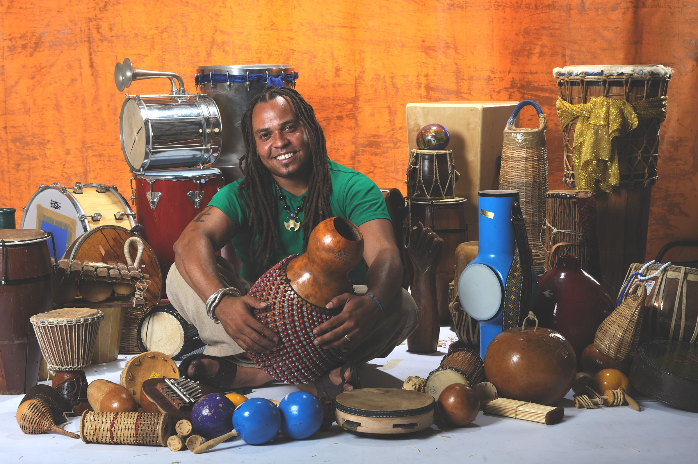 Dendê sits cross-legged, surrounded by various types of hand drums and other small percussion instruments