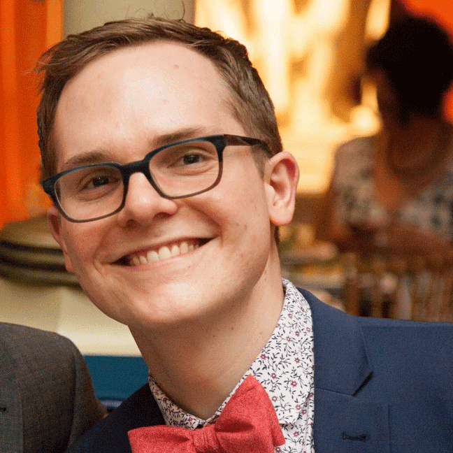 Herbie is photographed at an event wearing a navy blue suit with white patterned shirt and a snazzy red bow tie, with black rectangular glasses and a cheerful smile.