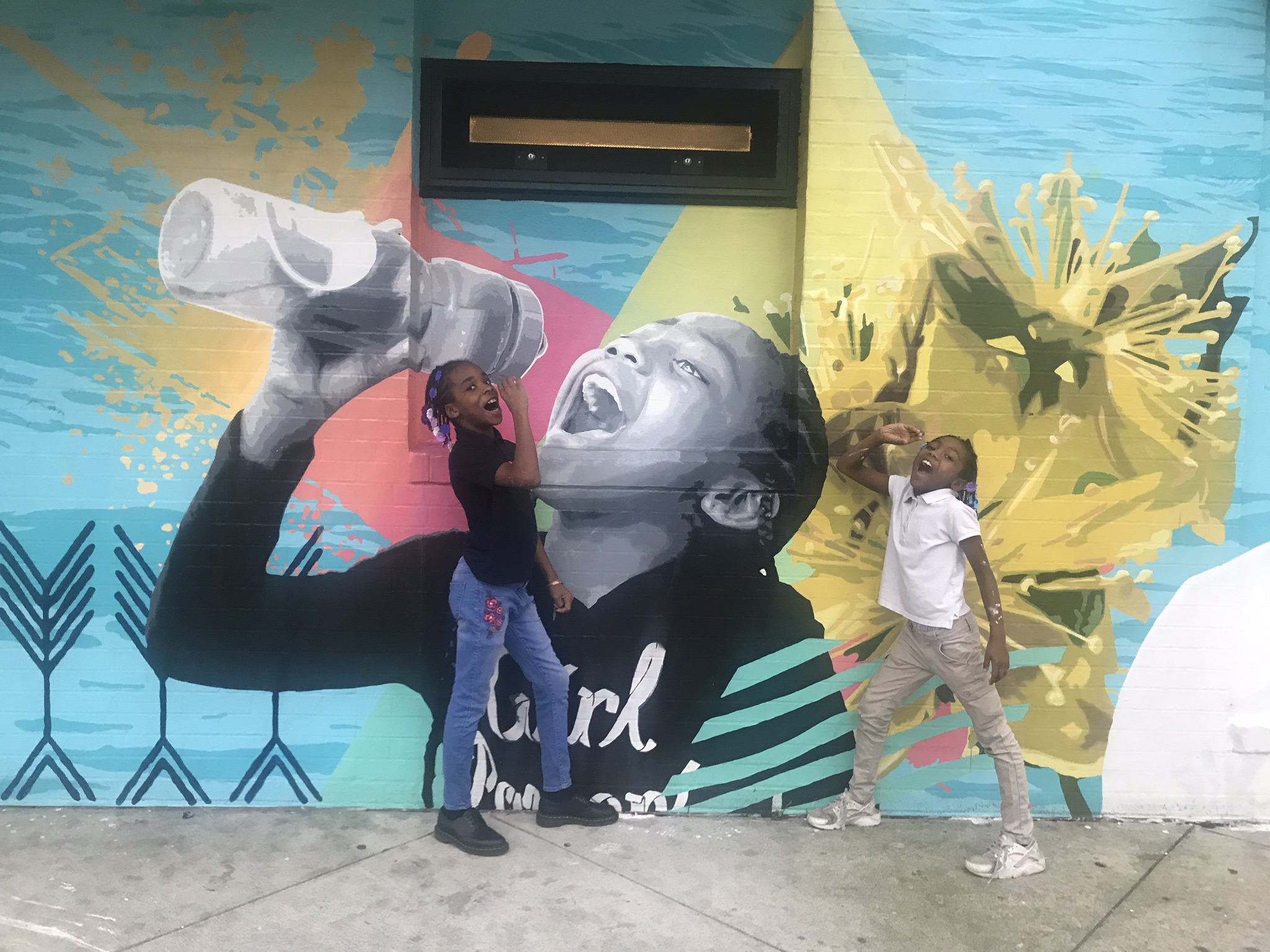 The mural show a young girl with dark skin and braids drinking from a reusable water bottle, painted in shades of grey with colorful abstract designs on a light blue background that looks like water. The model and another young girl stand in front of the wall mimicing her pose