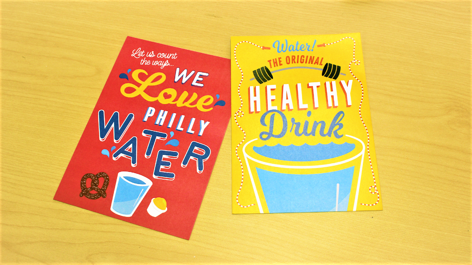 colorful postcards encouraging Philadelphians to drink tap water lay on a light wood table